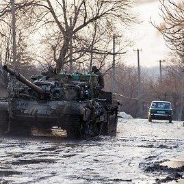 """AFP/""""Scanpix"""" nuotr./Traukiamas per apšaudymus apgadintas Ukrainos armijos tankas"""