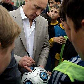 """AFP/""""Scanpix"""" nuotr./Vladimiras Putinas pasirašo ant futbolo kamuolio"""