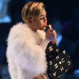 """Reuters""/""Scanpix"" nuotr./Miley Cyrus užsirūkė ant scenos"