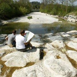 """""""Reuters""""/""""Scanpix"""" nuotr./Vyrai sėdi išdžiuvusioje Tioso upės vagoje"""