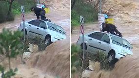 Galinga vandens srovė užnešė automobilį ant akmenų ir ant stogo įkalino vairuotoją