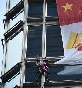 """Prancūzas """"žmogus voras"""" su """"taikos plakatu"""" užkopė į Honkongo dangoraižį"""