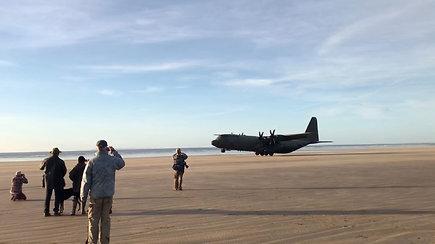 Netikėtai paplūdimyje nusileidęs didžiulis karinis lėktuvas nustebino susirinkusius
