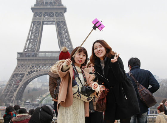 123rf.com nuotr./Turistės darosi asmenukę Paryžiuje prie Eifelio bokšto