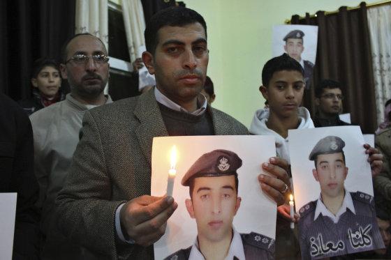 """Reuters""/""Scanpix"" nuotr./Jordanijos piloto Muazo al Kasasbecho (Muath al-Kasaesbeh) portretą laiko jo brolis"