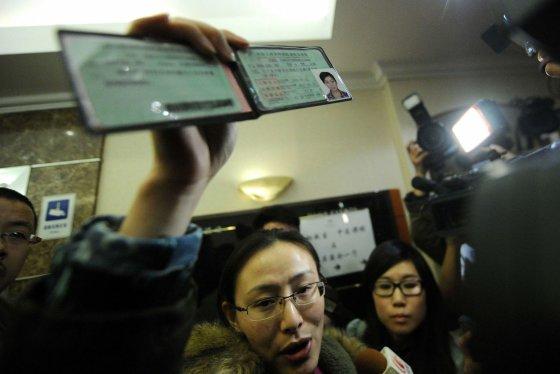 """""""Reuters""""/""""Scanpix"""" nuotr./Moteris rodo pradingusio lėktuvo keleivio vairuotojo pažymėjimą"""
