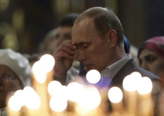"""AFP/""""Scanpix"""" nuotr./Vladimiras Putinas ortodoksų Kalėdų pamaldose"""