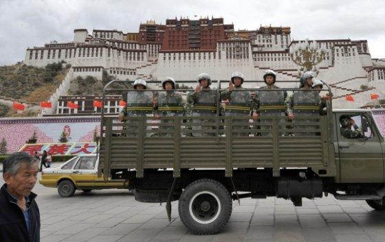 """AFP/""""Scanpix"""" nuotr./Kinijos riaušių policija patruliuoja prie Potalos rūmų Tibeto sostinėje Lhasoje."""