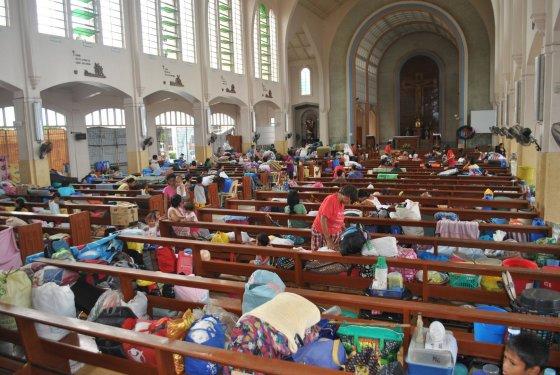 """AFP/""""Scanpix"""" nuotr./Prie Filipinų artėjant taifūnui žmonės apsistojo bažnyčioje"""
