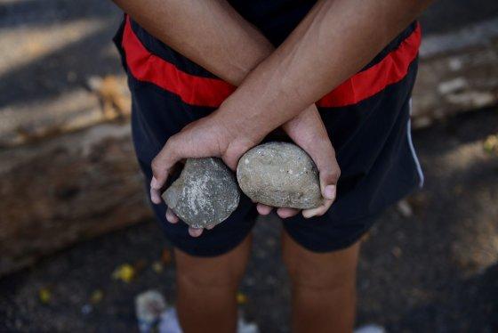 """AFP/""""Scanpix"""" nuotr./Akmenys protestuotojo rankose"""