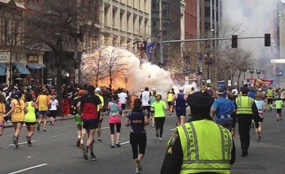 Bostono maratono dalyviai bėga link finišo, kairėje pusėje matomas prasidėjęs sprogimas.