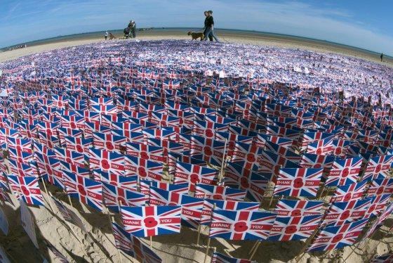 """""""Scanpix"""" nuotr./Didžiosios Britanijos vėliavėlės Normandijos paplūdimyje, kuriame prieš 70 metų išsilaipino britų kariai"""