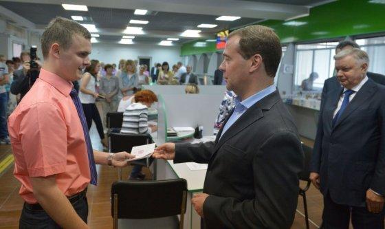 """AFP/""""Scanpix"""" nuotr./Dmitrijus Medvedevas įteikia Rusijos pasą jaunuoliui Federalinės migracijos tarnybos padalinyje Sevastopolyje"""