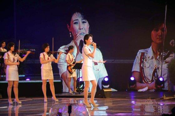 """""""Scanpix"""" nuotr./Kai grupės Moranbong daininkės per televiziją pasirodė ne tik trumpais sijonais, bet ir trumpomis šukuosenomis, Šiaurės Korėjos moterys suabejojo, kas leidžiama madoje, o kas ne"""
