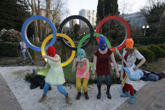 David Goldman/AP / Postimees.ru/Members of the punk group Pussy Riot, including Nadezhda Tolokonnikova in the aqua balaclava, center, and Maria Alekhina in the red balaclava, left, perform next to the Olympic rings in Sochi, Russia, on Wednesday, Feb. 19, 2014. Cossack militia attacked the punk group with horsewhips earlier in the