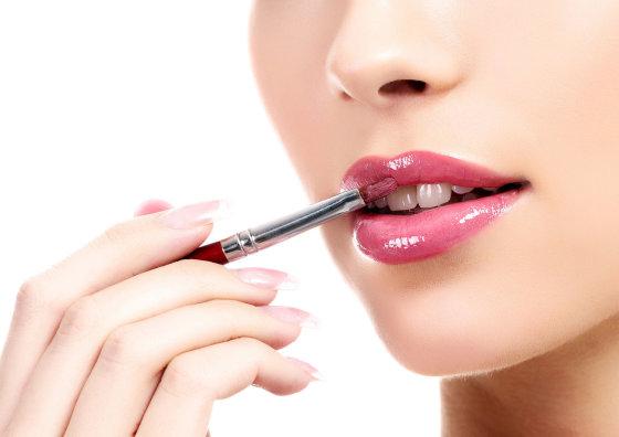 Shutterstock nuotr./Moteris blizgiu dažosi lūpas