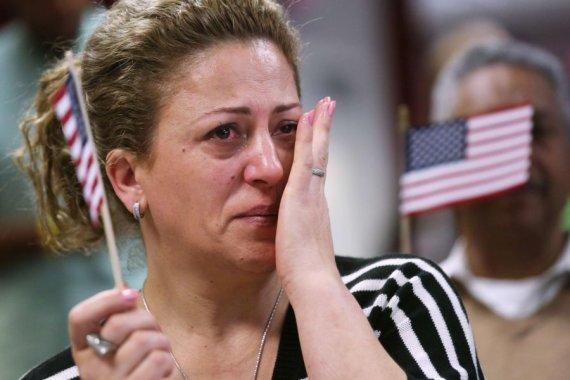AFP/Scanpix nuotr./Neseniai JAV pilietybę gavusi moteris braukia džiaugsmo ašarą.