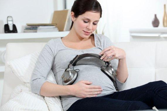 Fotolia nuotr./Nėščia moteris uždėjusi ausines ant pilvo