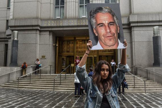 """AFP/""""Scanpix"""" nuotr./Mergina, laikanti nuotrauką su Jeffrey Epsteino atvaizdu"""