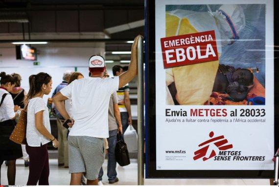 """""""Scanpix""""/""""SIPA"""" nuotr./Barselonos oro uoste esantis plakatas, perspėjantis apie Ebolos viruso grėsmę"""