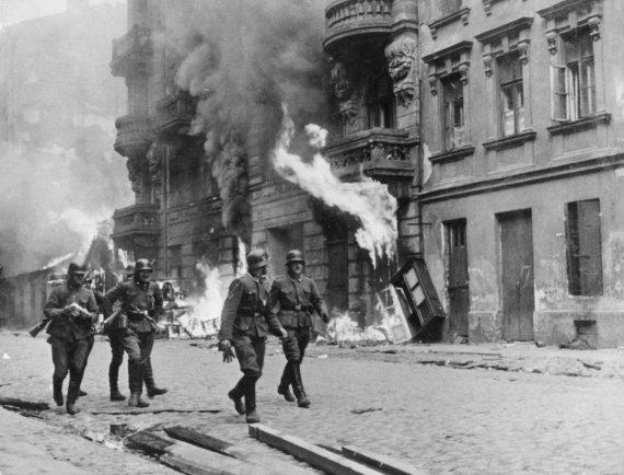 Vida Press nuotr./Vokiečių kareiviai 1943 m. eina pro padegtą Varšuvos getą, kuris po sukilimo buvo sudegintas iki pamatų