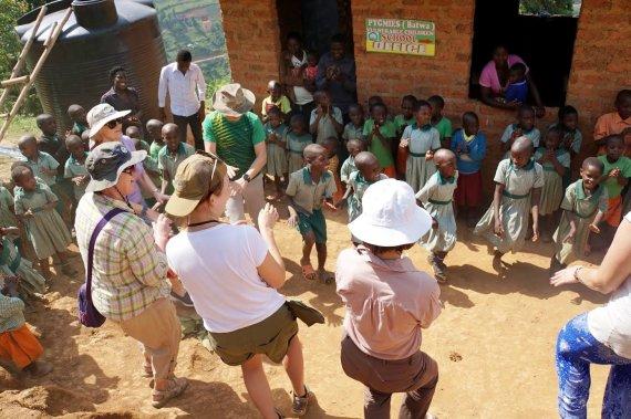 """Kelionių organizatoriaus """"GRŪDA"""" nuotr./Kaimo mokyklos vaikai """"GRŪDOS"""" keliautojus pasitinka su šokiais ir dainomis, Uganda"""
