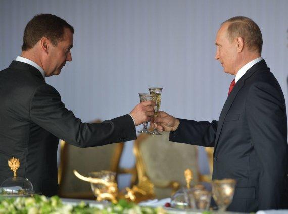 """""""Scanpix""""/AP nuotr./Vladimiras Putinas ir Dmitrijus Medvedevas susidaužia šampano taurėmis per šventinį priėmimą Maskvoje"""