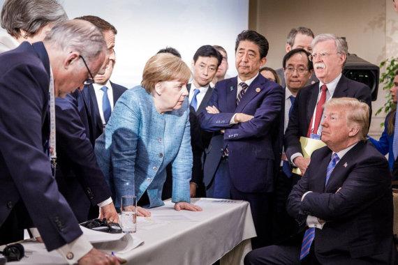 """AFP/""""Scanpix"""" nuotr./A.Merkel kalbasi su D.Trumpu kitų pasaulio lyderių apsuptyje"""