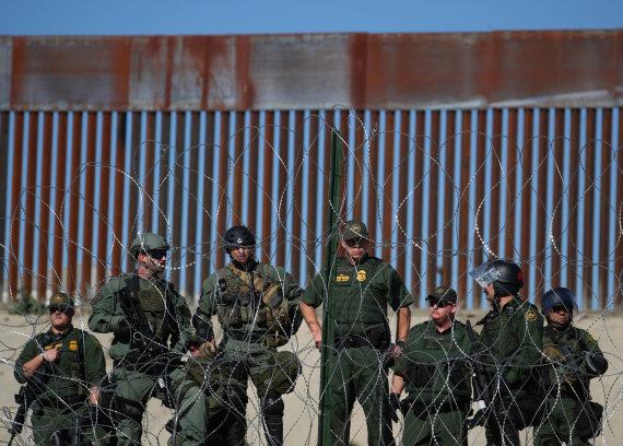 """""""Reuters""""/""""Scanpix"""" nuotr./JAV pasieniečiai prie tvoros palei Amerikos ir Meksikos sieną"""