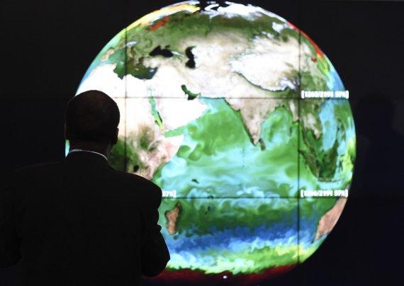 """AFP/""""Scanpix"""" nuotr./Klimato kaitos konferencijos dalyvis"""