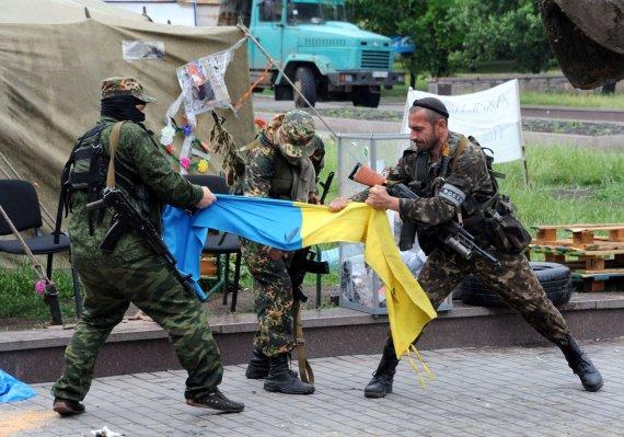"""AFP/""""Scanpix"""" nuotr./Prorusiški teroristai plėšo Ukrainos vėliavą Donecke"""