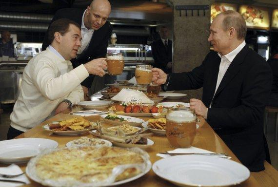 """""""Reuters""""/""""Scanpix"""" nuotr./Dmitrijus Medvedevas ir Vladimiras Putinas prie vaišių stalo"""