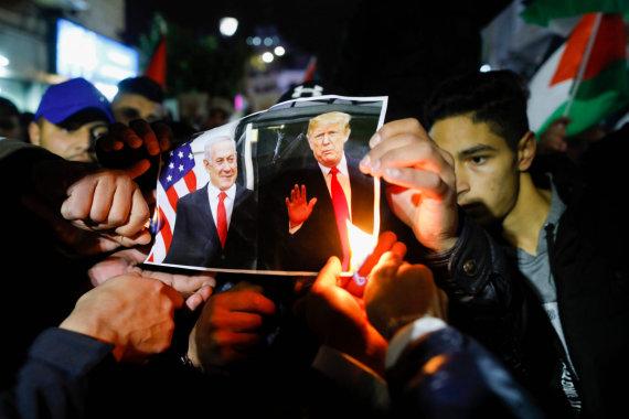 """AFP/""""Scanpix"""" nuotr./Ramaloje protestuojantys palestiniečiai degina D.Trumpo ir B.Netanyahu nuotrauką."""