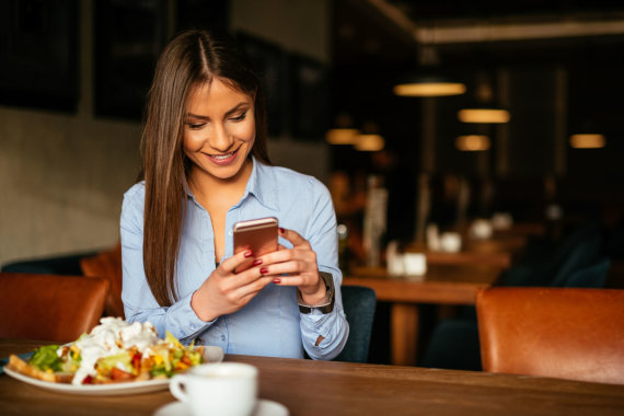 Fotolia nuotr./Mergina valgydama naršo telefone.