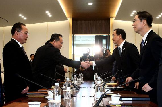 """AFP/""""Scanpix"""" nuotr./Sveikinasi Pietų Korėjos susivienijimo ministras Cho Myoung-gyonas (antras iš dešinės) ir Šiaurės Korėjos delegacijos vadovas Ri Son Gwonas (antras iš kairės)"""