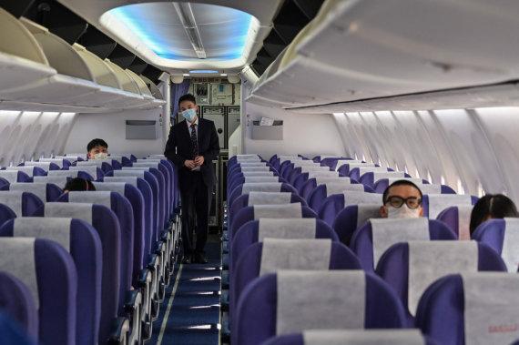 """AFP/""""Scanpix"""" nuotr./Žmonės lėktuve su apsauginėmis kaukėmis"""