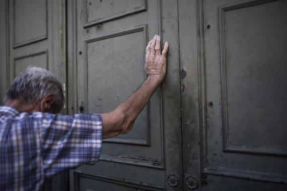 """AFP/""""Scanpix"""" nuotr./Pensininkas prie Graikijos banko durų"""