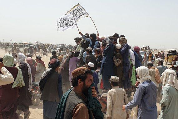 """AFP/""""Scanpix"""" nuotr./Žmonės mojuoja Talibano vėliavomis Afganistano ir Pakistano pasienyje"""
