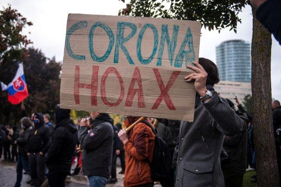 """AFP/""""Scanpix"""" nuotr./Protestuotojas Slovakijoje laiko plakatą su užrašu """"korona apgaulė"""""""