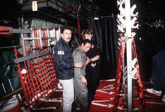 Wikipedia.org nuotr./JAV Narkotikų kontrolės administracijos pareigūnų lydimas Manuelis Noriega lėktuve, skrisiančiame į JAV (1990 m. sausio 3 d.)