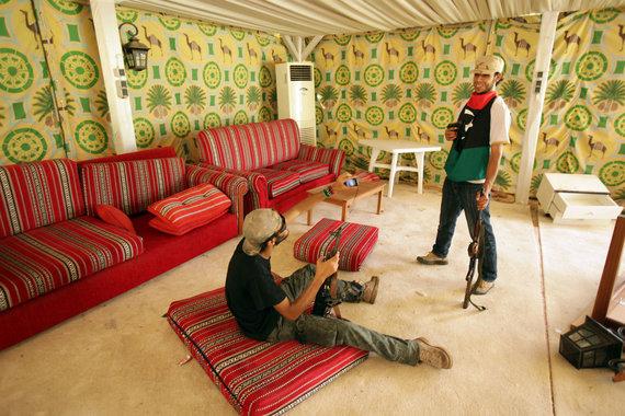 """AFP/""""Scanpix"""" nuotr./Sukilėliai pozuoja nuotraukoms Muamaro Kadhafi palapinėje, kurioje jis rengdavo priėmimus užsienio svečiams. (2011 m. rugpjūtis)"""