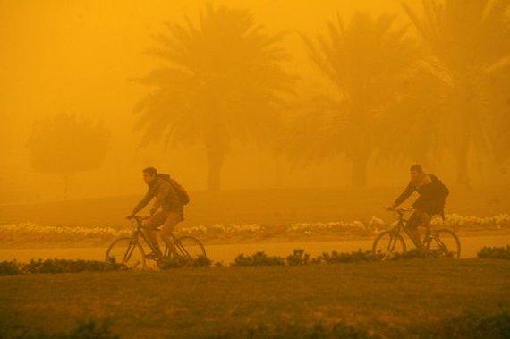 """AFP/""""Scanpix"""" nuotr./Smėlio audra užklupo dviratininkus"""