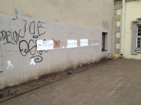 """Vilniaus miesto sienos nukabinėtos plakatais """"War is over?"""""""