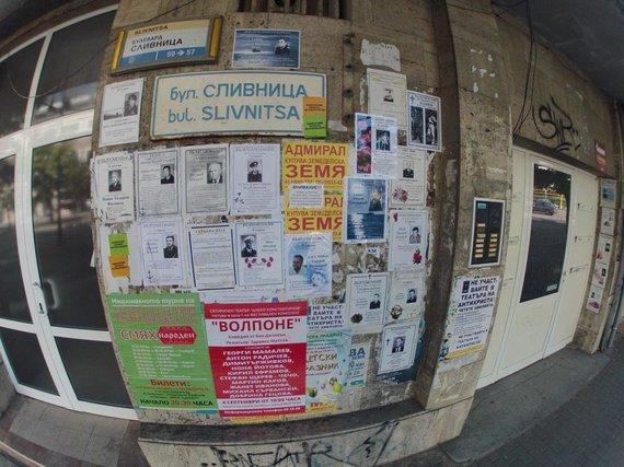 Ant pastato sienų iškabinti lapai su čia mirusių žmonių nuotraukomis ir nekrologais