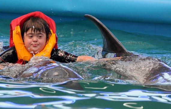 """AFP/""""Scanpix"""" nuotr./Dauno sindromo paveiktų vaikų terapija su delfinais"""