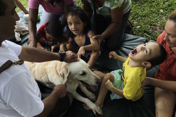 """""""Reuters""""/""""Scanpix"""" nuotr./Ištreniruota kalytė Fiona dalyvauja terapijos sesijoje, skirtoje vaikams, turintiems psichinių ir fizinių sutrikimų (Dauno sindromas, cerebrinis paralyžius, autizmas ir pan.)"""
