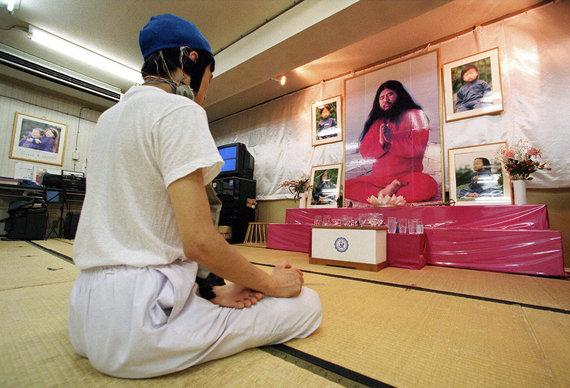 """""""Reuters""""/""""Scanpix"""" nuotr./Aum Shinrikyo narys medituoja prieš S.Asuhara paveikslą"""