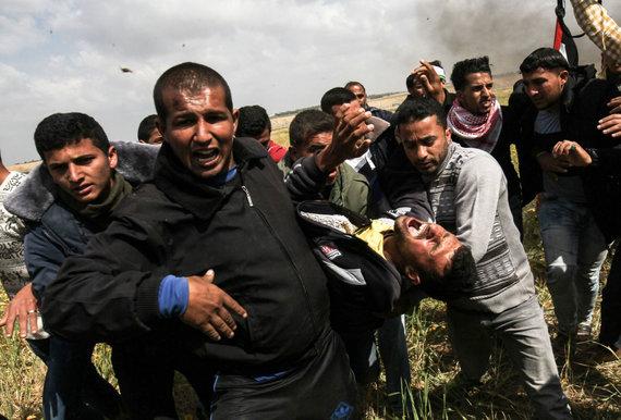 """AFP/""""Scanpix"""" nuotr./F.al Raqibas (priekyje, pačioje kairėje) neša vieną sužeistąjį"""