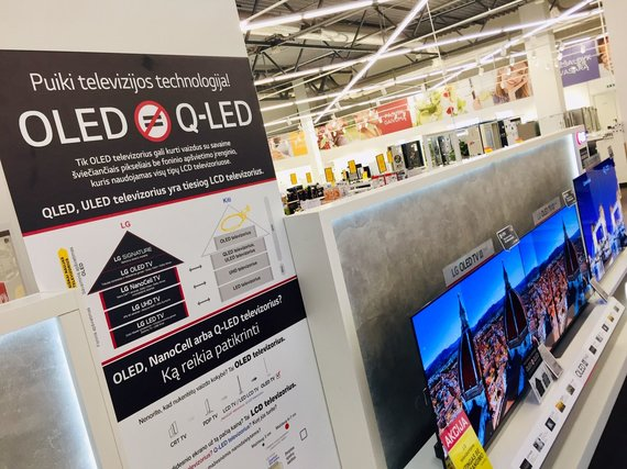 """Valdo Kopūsto / 15min nuotr./Draugiškos konkurencijos ženklas: lentelėje pateikiamas išaiškinimas, kad LG vystoma OLED technologija yra pranešesnė už """"Samsung"""" kuriamus QLED ekranus"""