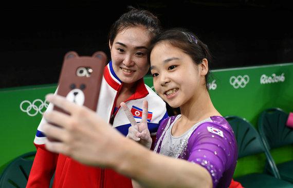 """""""Reuters""""/""""Scanpix"""" nuotr./Pietų korėjietė Lee Eun-Ju (dešinėje) fotografuojasi su šiaurės korėjiete Hong Un Jong"""